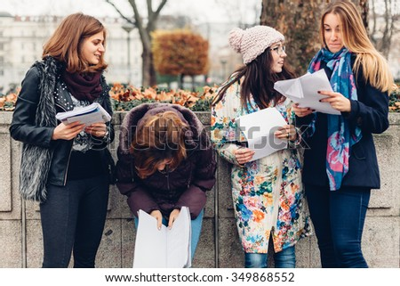 Happy girls checking the results in the park after the exam - stock photo