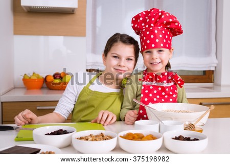 Happy girls cooking together. Young smiling children kids family having fun preparing granola in kitchen at home. Cooking concept. Sisters teamwork