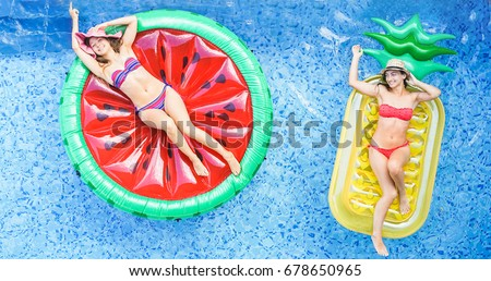 Happy Girls Floating With Tropical Fruit Lilos Inside Swimming Pool