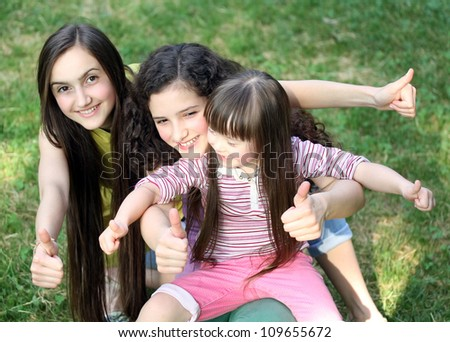 Happy girls giving thumbs up in the park. - stock photo