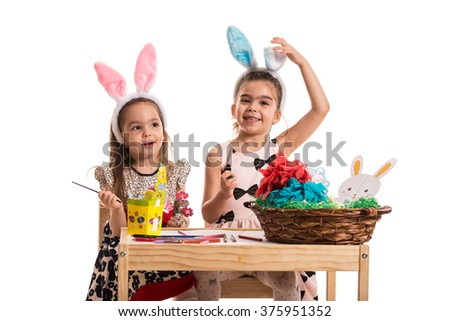 Happy girls making Easter decorations and sitting at table - stock photo