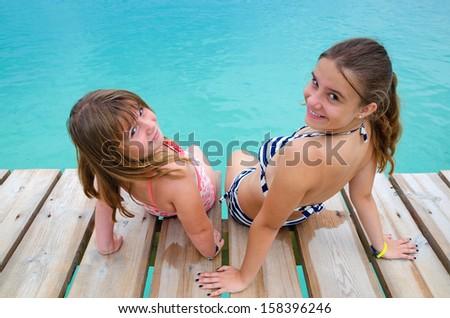 Happy girls on tropical bridge - stock photo
