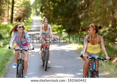 Happy girls riding bicycles outside enjoy summer sport - stock photo