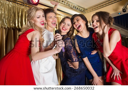 happy girls singing into a microphone - stock photo
