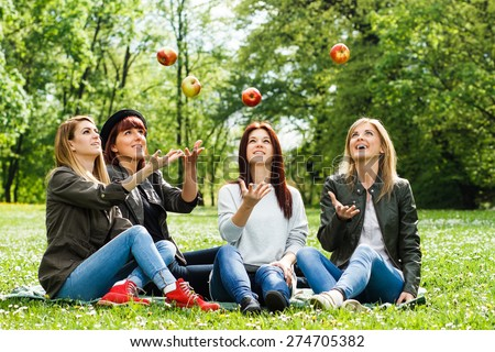 Happy girls throwing apples in the park.Healthy snack for young girls - stock photo