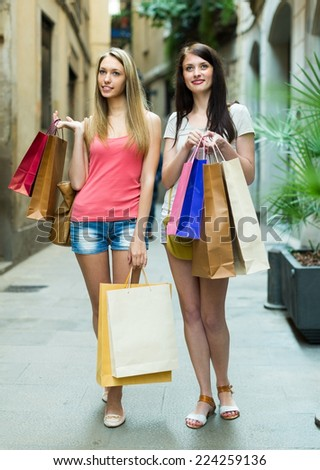 Happy girls walking by street with shopping bags in hands and smiling