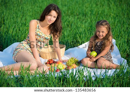 Happy girlswith fruits on green grass at spring or summer park picnic - stock photo