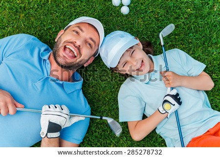 Happy golfers. Top view of cheerful little boy and his father holding golf clubs and smiling while lying on the green grass  - stock photo