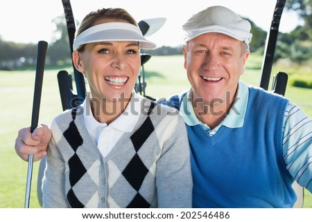 Happy golfing couple sitting in golf buggy smiling at camera on a sunny day at the golf course - stock photo