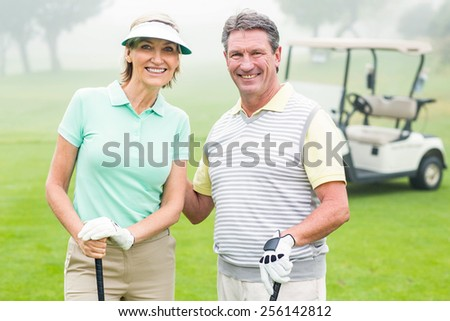 Happy golfing couple with golf buggy behind on a foggy day at the golf course - stock photo