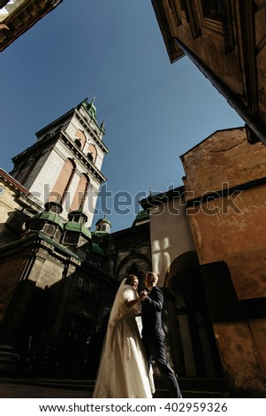 happy gorgeous bride and stylish handsome groom dancing on background of old buildings with amazing sky view in sunlight patio