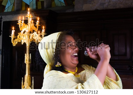 Happy gospel singer with microphone singing during mass - stock photo