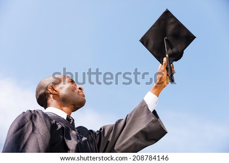 Happy graduate. Low angle view of happy young African man in graduation gown holding his mortar board against blue sky  - stock photo