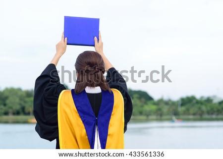 Happy graduated student girl at graduation ceremony - stock photo
