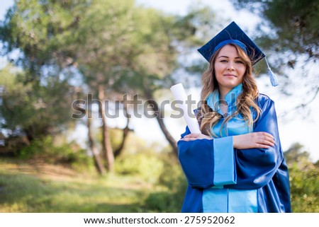 Happy Graduating Mixed Race Woman In Cap and Gown Celebrating on Campus - stock photo
