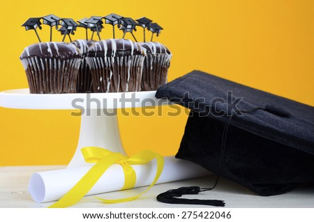 Happy Graduation Day party chocolate cupcakes with graduation cap hat topper decorations, in yellow, black and white party theme.  - stock photo