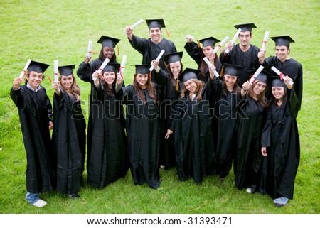 happy graduation students full of success outdoors - stock photo