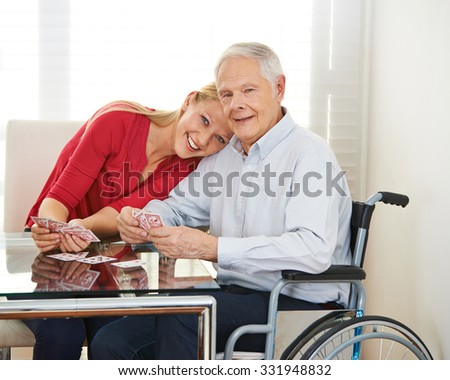 Happy granddaughter playing cards with grandfather in wheelchair - stock photo