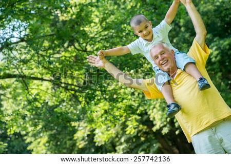 happy grandfather and child have fun and play in park on beautiful  sunny day - stock photo