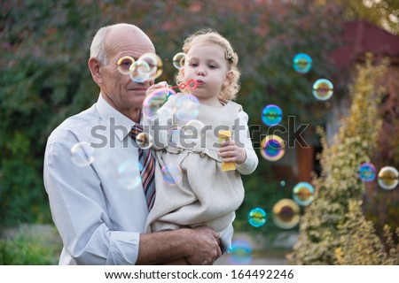 Happy grandfather and cute curly granddaughter blowing soap bubbles - stock photo
