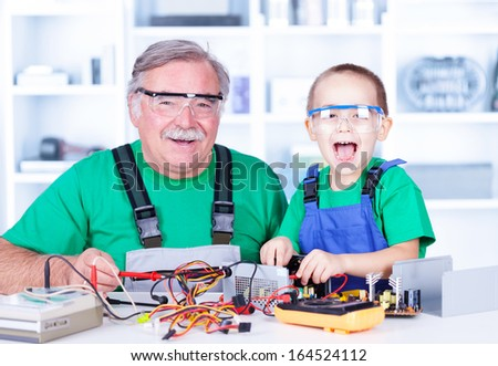 Happy grandfather and grandchild working together in workshop - stock photo