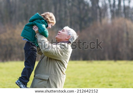 Happy grandfather and his little grandson having fun together outdoors - stock photo