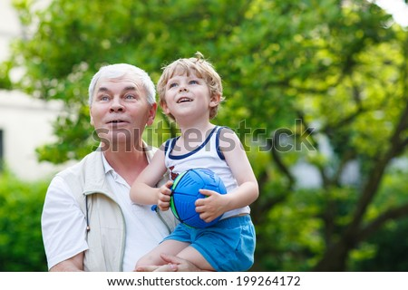 Happy grandfather playing with little grandchild ball in summer