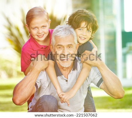 Happy grandfather playing with two grandchildren in a summer garden