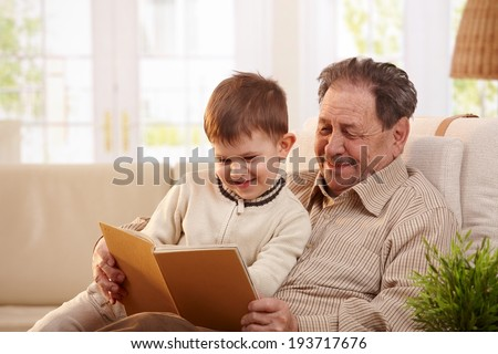 Happy grandfather sitting in armchair and reading book to his grandson, smiling. - stock photo