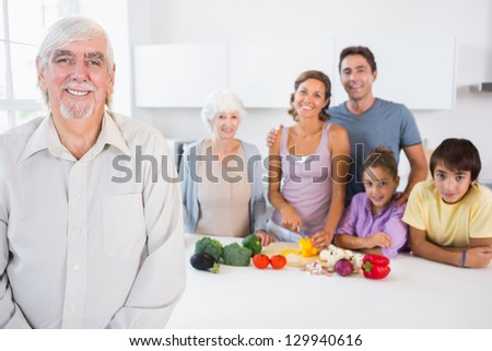 Happy grandfather standing by kitchen counter with family behind him
