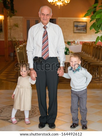 Happy grandfather with his grandchildren at restaurant before birthday party - stock photo