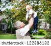 Happy grandfather with little baby boy in summer garden - stock photo