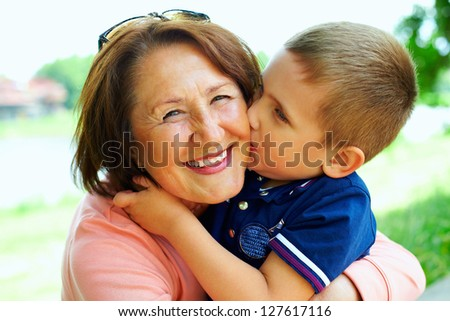 happy grandma with grandson embracing outdoor - stock photo