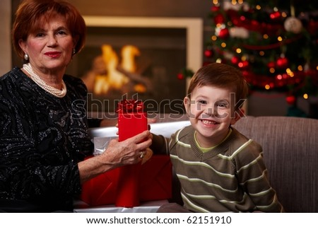 Happy grandmother and grandchild sitting on sofa at home, holding christmas gift, smiling.? - stock photo