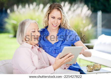 Happy grandmother and granddaughter using digital tablet at nursing home porch - stock photo