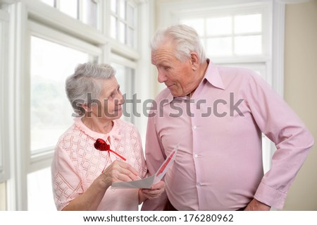happy grandmother and grandfather with postcard for valentine's day - stock photo