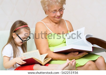 Happy grandmother and her granddaughter are reading books at home - stock photo
