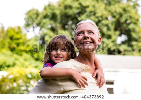 Happy grandmother carrying grandson at yard