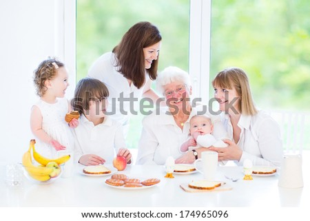 Happy grandmother enjoying breakfast with her daughter and grandchildren - teenage boy, funny curly toddler girl with and newborn baby - sitting in a white dining room with a big garden view window - stock photo