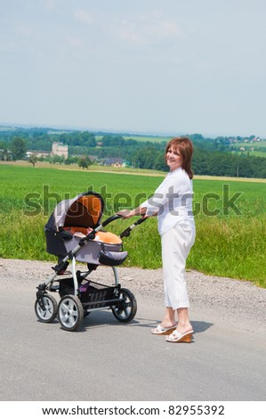 happy grandmother in walk with stroller