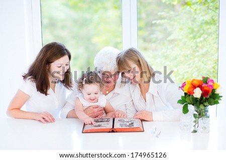 Happy grandmother watching black and white photo album with her daughter and grandchildren in a beautiful white dining room with a big garden view window - stock photo