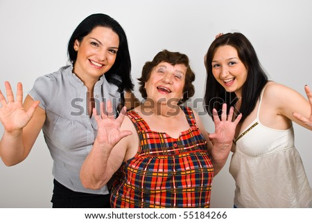Happy grandmother with granddaughters laughing together and waving hands in front of camera