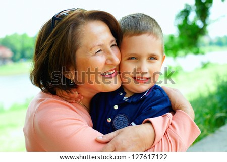 happy grandmother with grandson having fun outside - stock photo