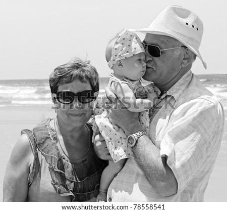 happy grandpa and grandma are holding a little granddaughter. Background - the sea. - stock photo