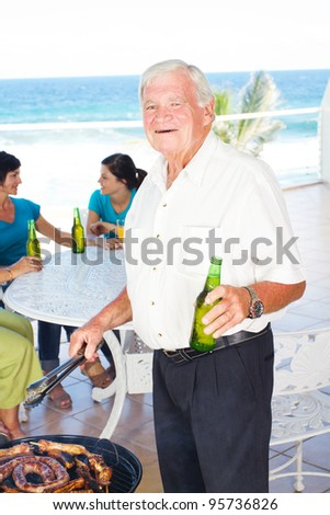 happy grandpa doing barbeque for the family in background - stock photo