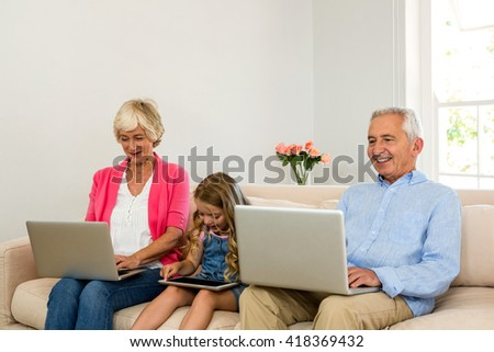 Happy grandparents and girl using technology while sitting on sofa - stock photo