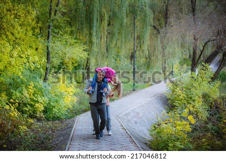 happy grandparents and granddaughter in the autumn park - stock photo