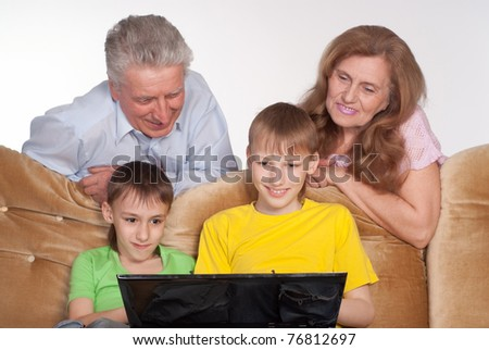happy grandparents and grandsons with a laptop