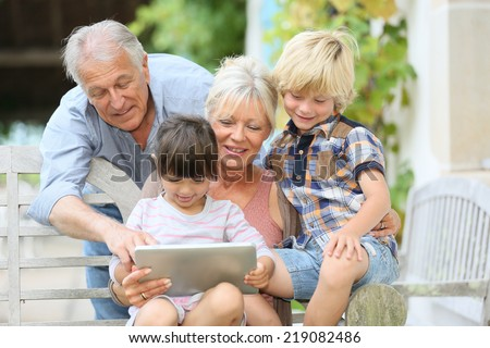 Happy grandparents playing game on tablet with kids - stock photo