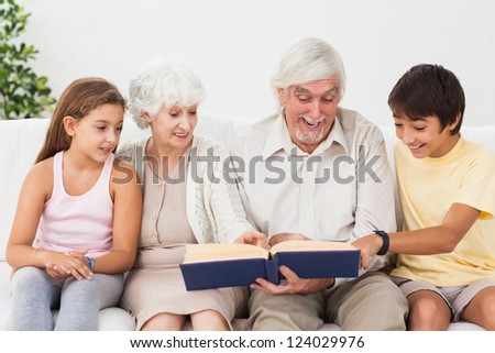 Happy grandparents reading book with grandchildren on the couch - stock photo